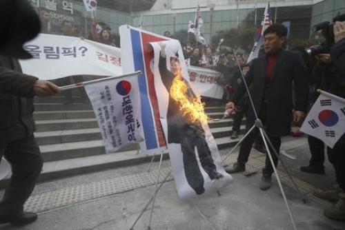 Manifestanti bruciano foto di Kim a Seul